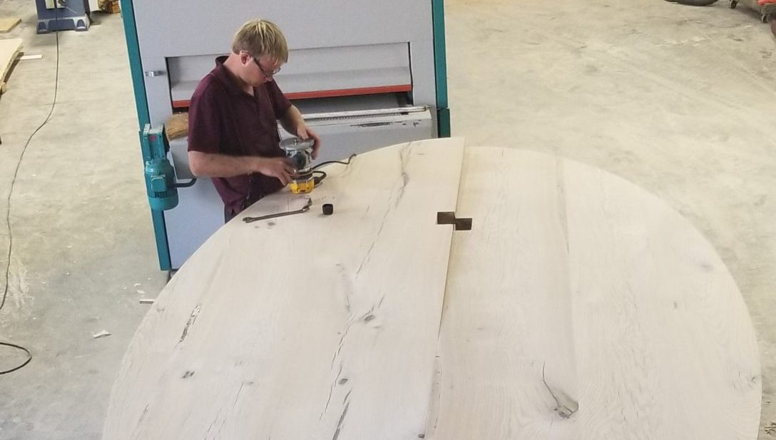 man hand-sanding a table